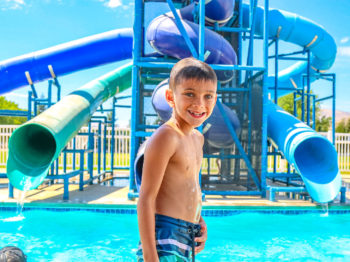 A camper standing in front of the water slides by the pool.
