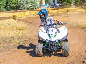A camper riding an ATV with a helmet on.