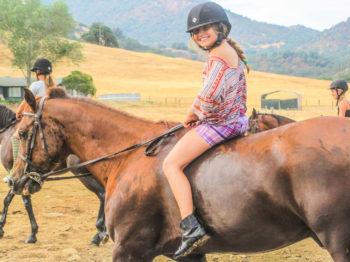 A camper riding bareback on a horse.