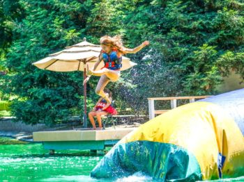 A camper jumping off a blob in the lake.