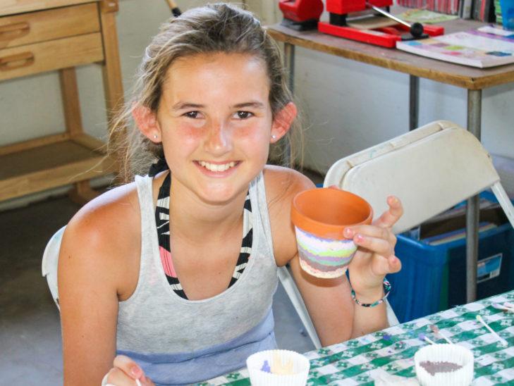 A camper painting a ceramic pot.