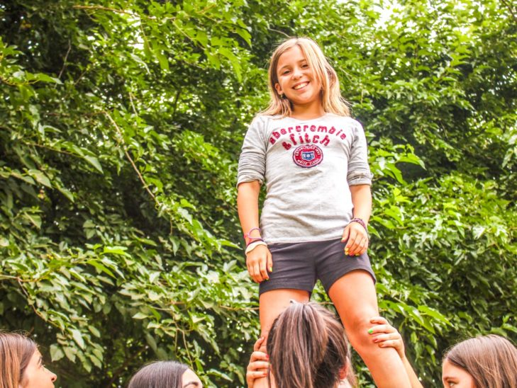 A camper standing up while learning how to cheer