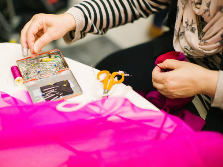 A person sewing a piece of fabric.