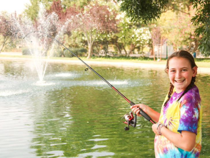 A camper smiling while fishing.
