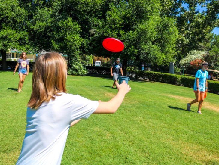 A camper throwing a frisbee during a game of frisbee golf.