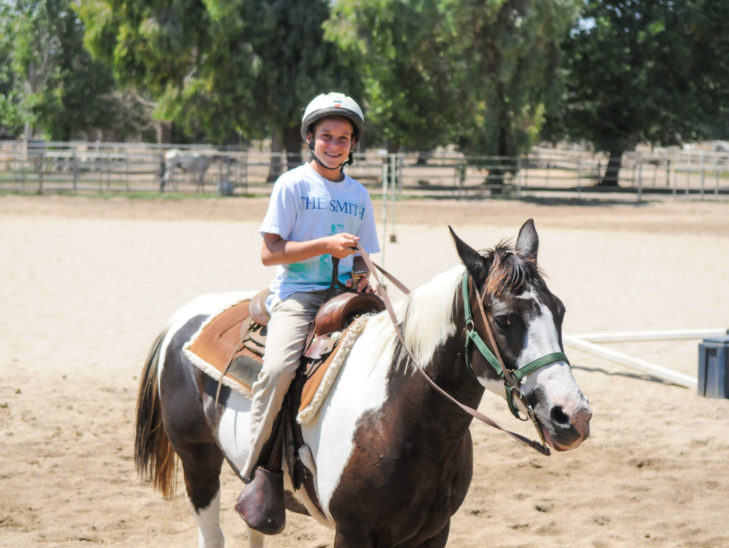 A camper smiling while on a horse.