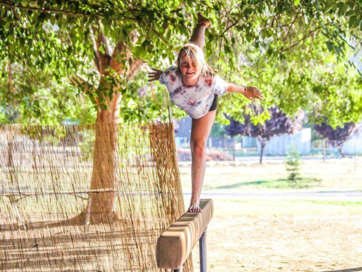 A camper practicing her gymnastics skills on the balance beam.