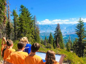 Campers looking over a mountain range in the distance while on a hike.