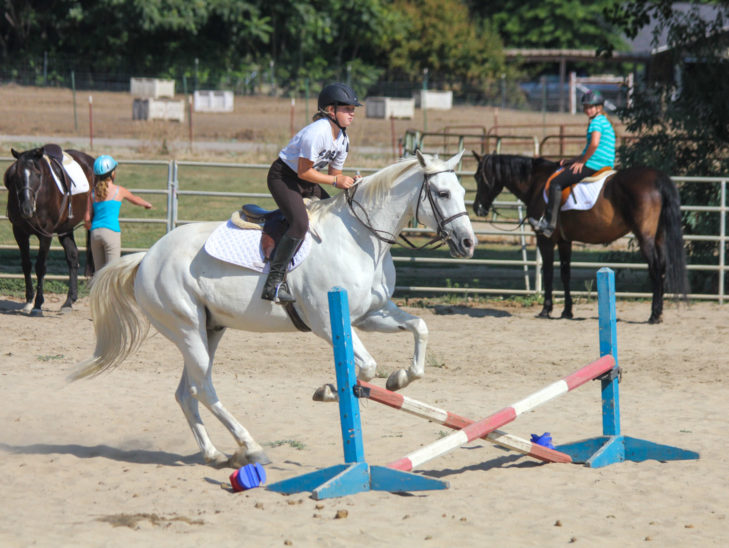 A camper jumping across an obstacle on horseback.