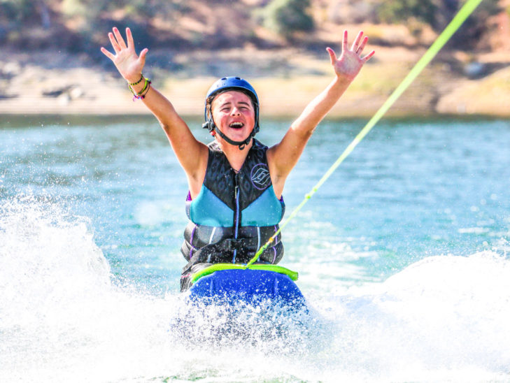 A camper with their hands in the air while kneeboarding.