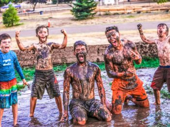 Campers yelling with their hands in the air in the mud during a game of gaga.