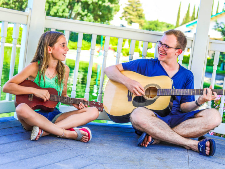 A camper getting a lesson on how to play the guitar.