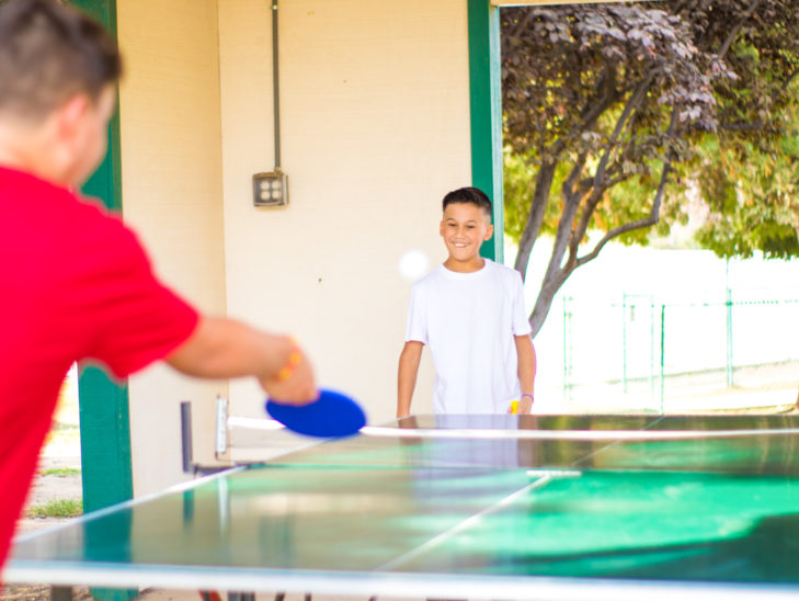 Two campers playing ping pong.