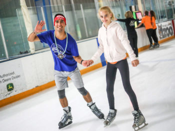 A camper learning how to ice skate.