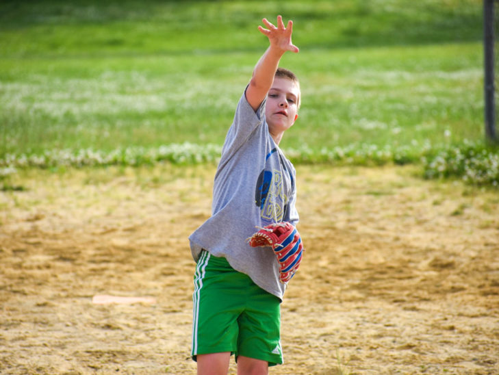 A camper throwing a ball while playing softball.