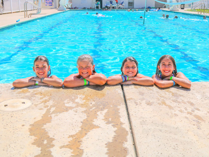Campers leaning on the edge of the pool and smiling.
