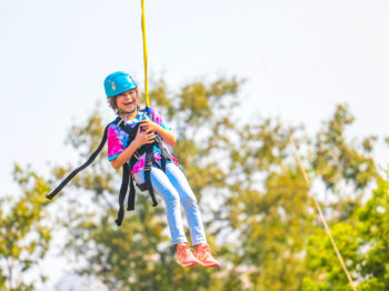 A camper laughing while going down a zip line.