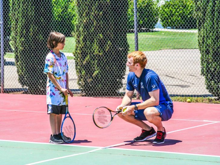 A camper learning how to play tennis