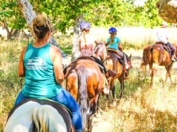 Campers riding along a trail on horseback.