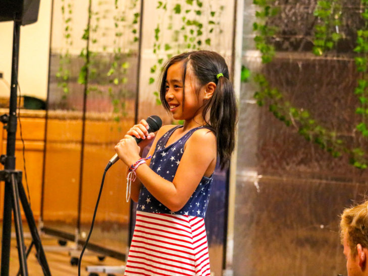 A camper standing with a microphone practicing her vocals.