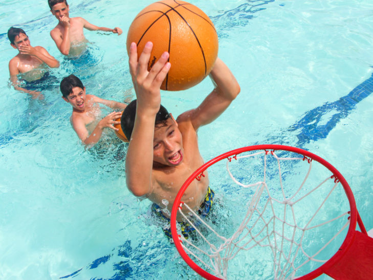 Campers dunking a basketball in the water.
