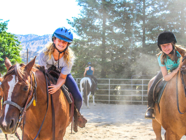 Campers riding horses.