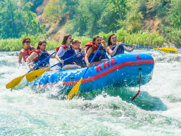 Campers whitewater rafting on a river.