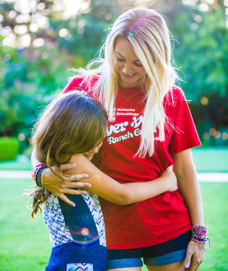 A camper and her family member hugging and smiling.