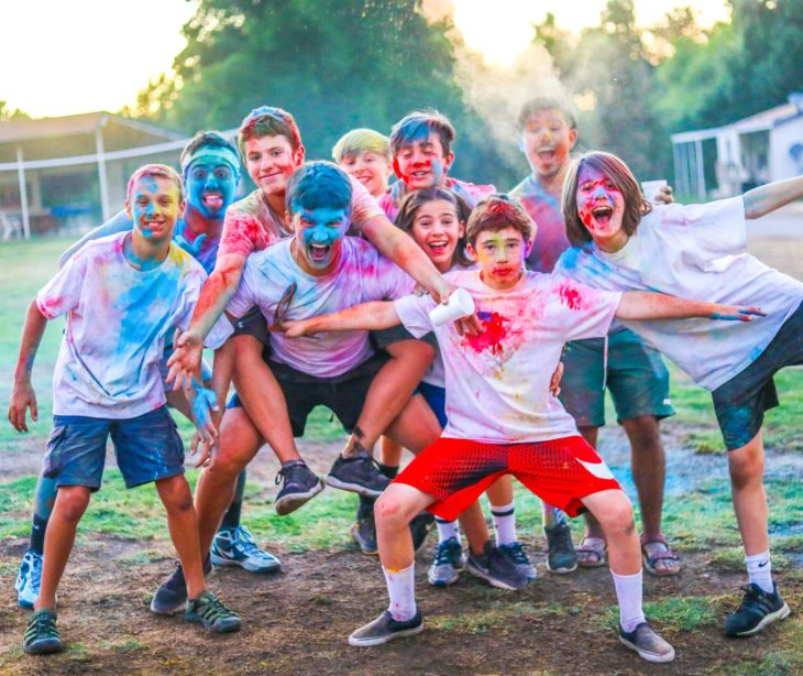 Campers with colorful dust on their clothes having a good time.