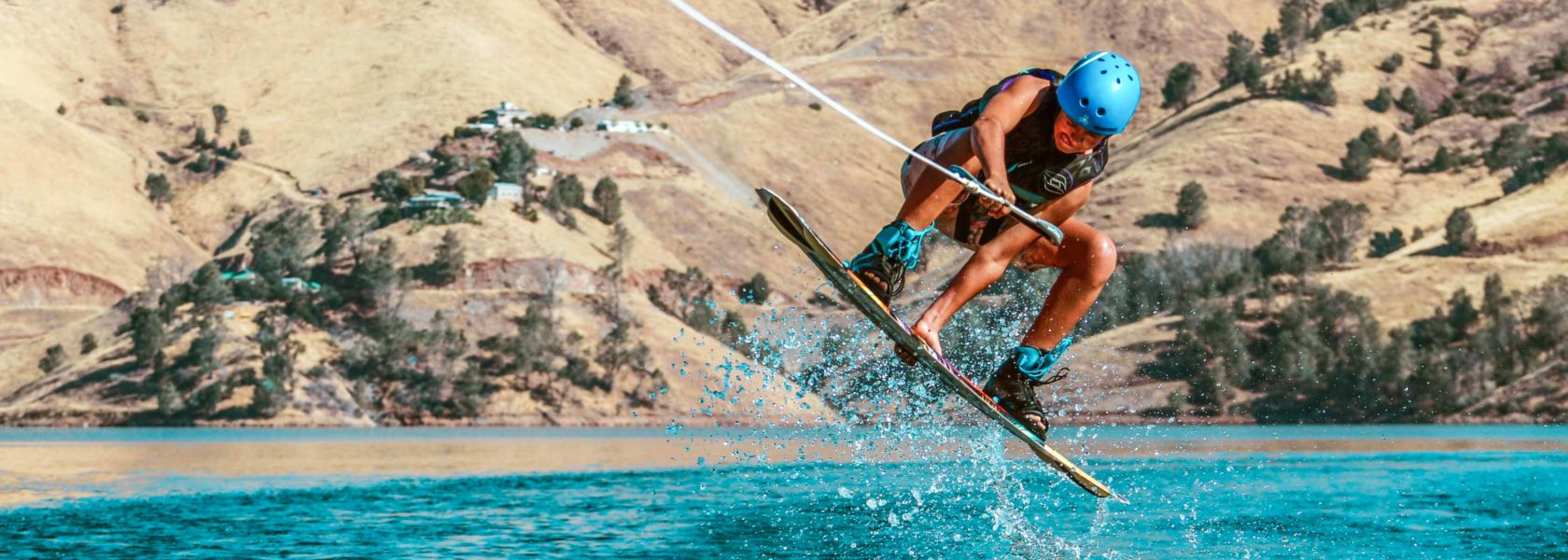 A camper wakeboarding and jumping in the air.