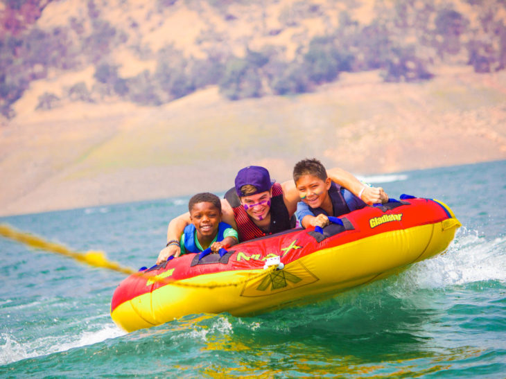Campers having fun tubing on a lake.