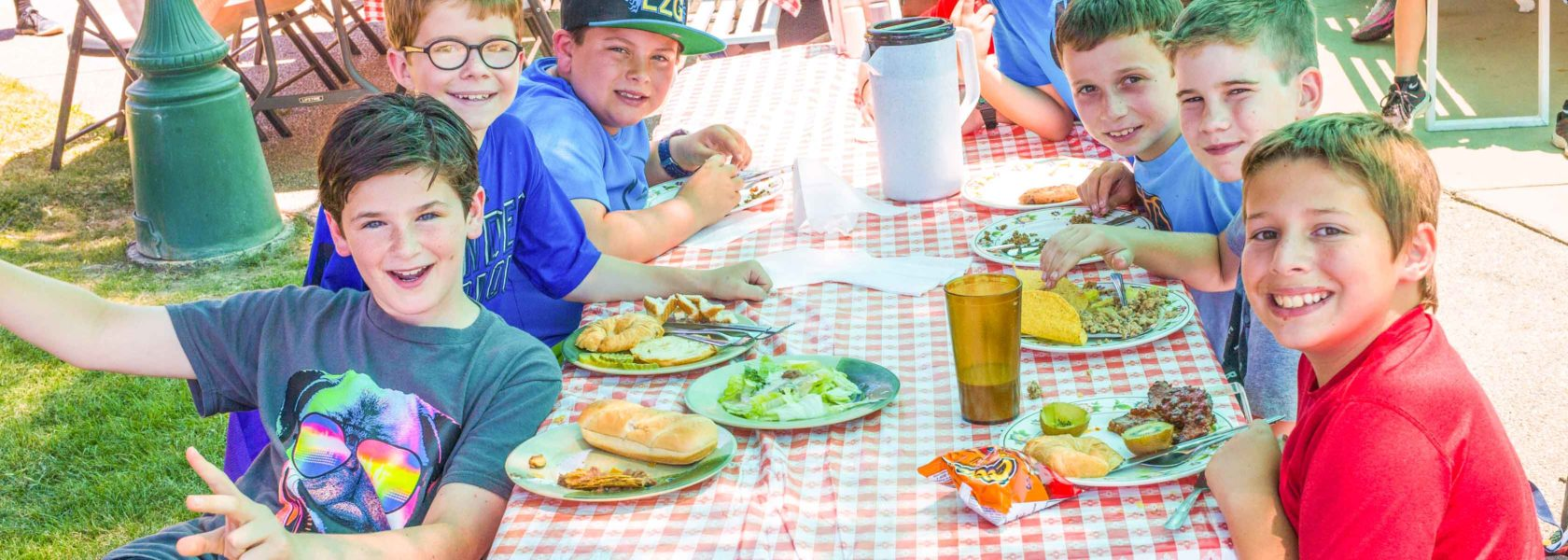 Campers sitting at a picnic table eating food.
