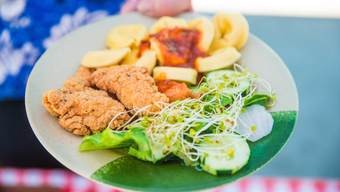Chicken tenders, a salad, and tortellini on a plate.