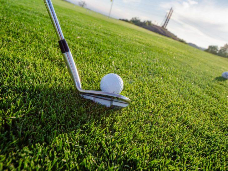 A golf club hitting a golf ball