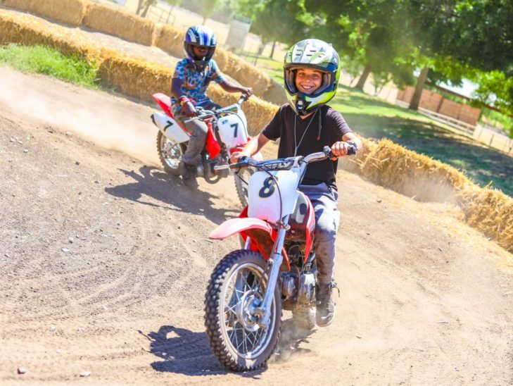 Campers riding on a course on mini bikes.
