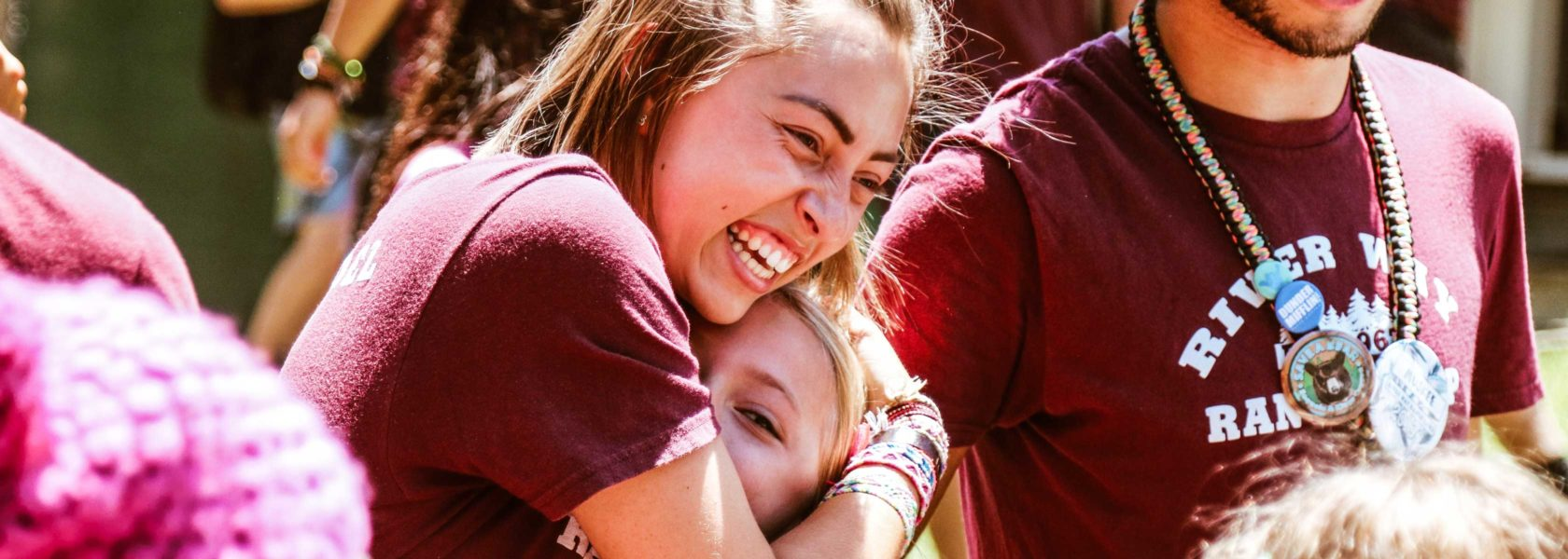 A counselor hugging a camper and smiling.