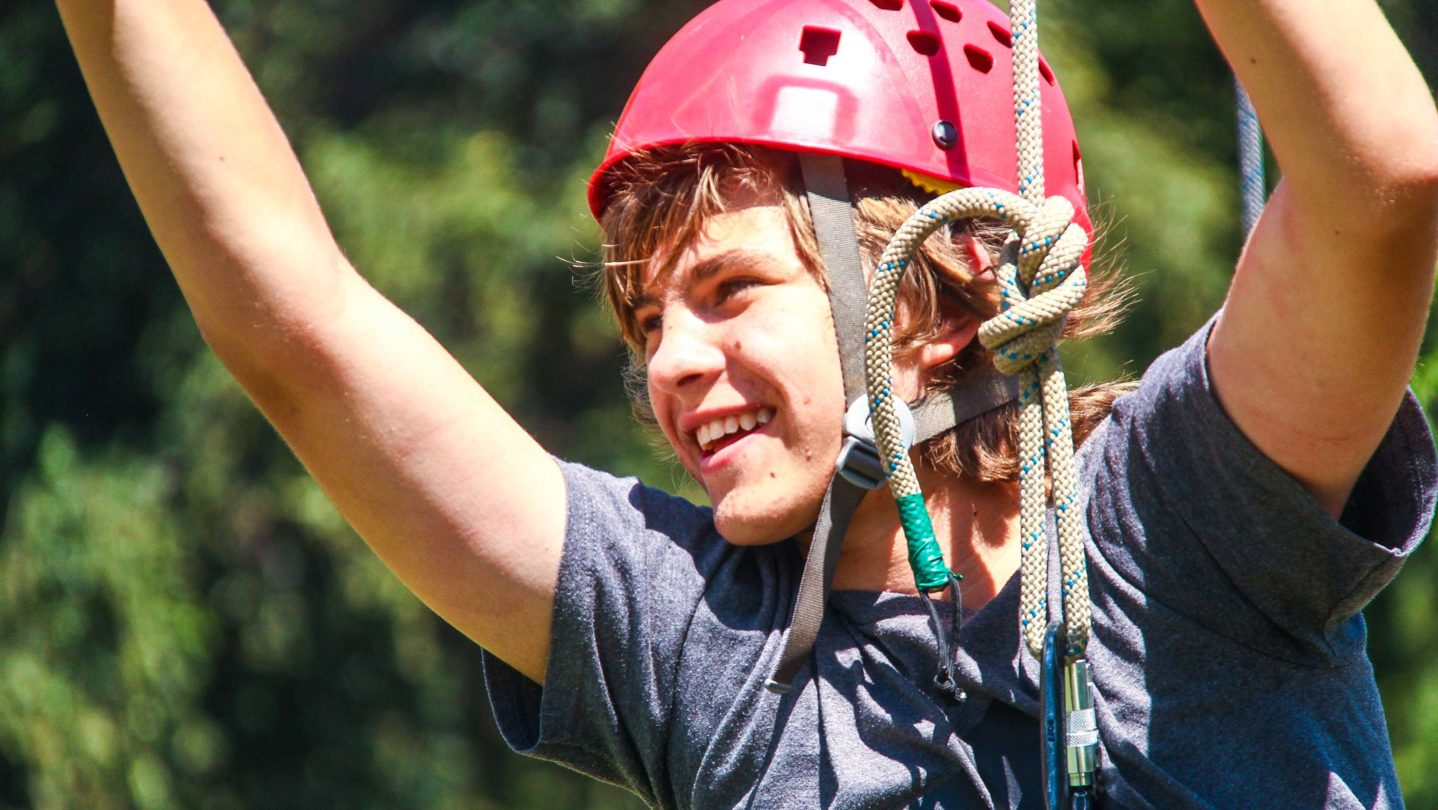 A camper smiling while on a zipline.