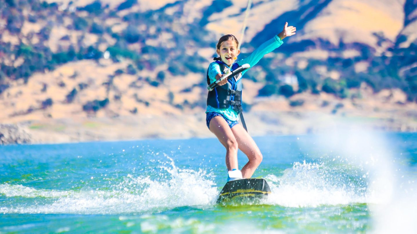 A camper with her hand up in the air while wake boarding.
