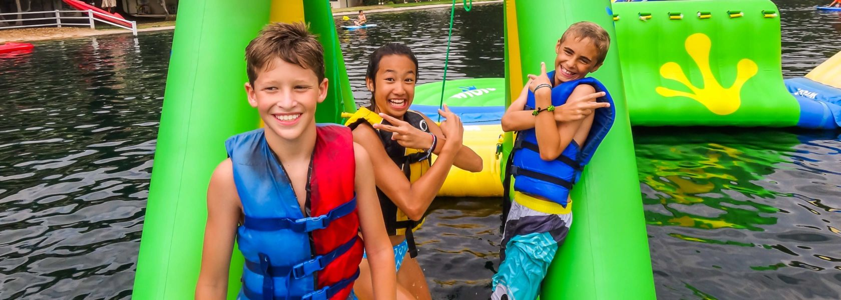 Campers playing on the water adventure course