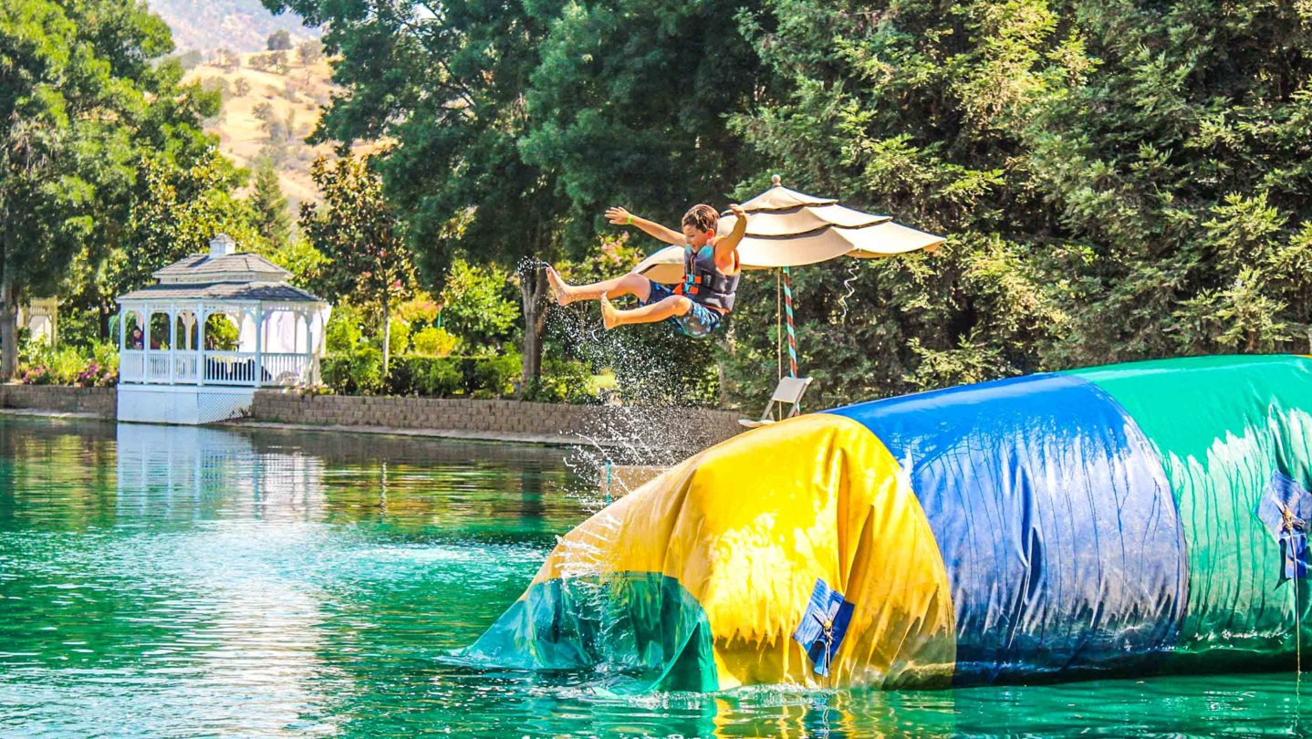 A camper jumping on an inflatable bouncy trampoline
