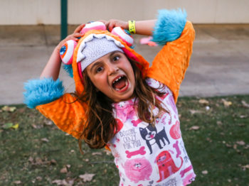 A camper smiling and laughing at the camera while dressed in colorful clothes.