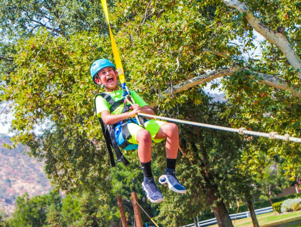 A camper on a zip line laughing