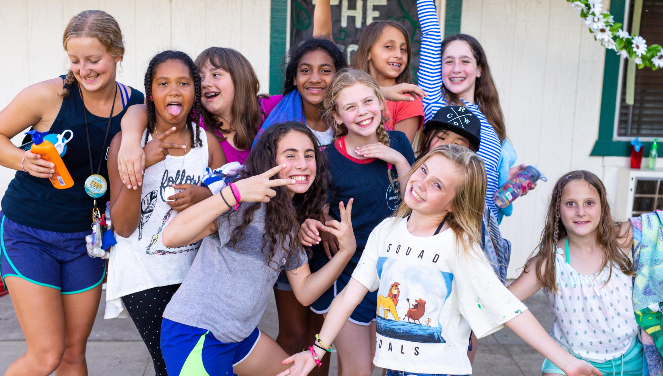 Campers smiling and making silly poses for the camera.