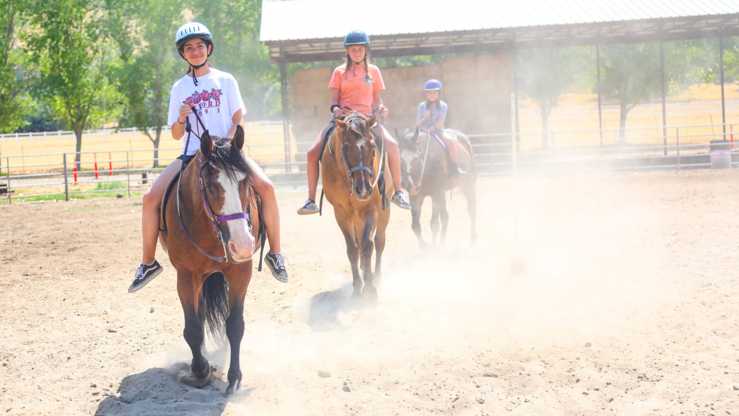 Campers riding horses