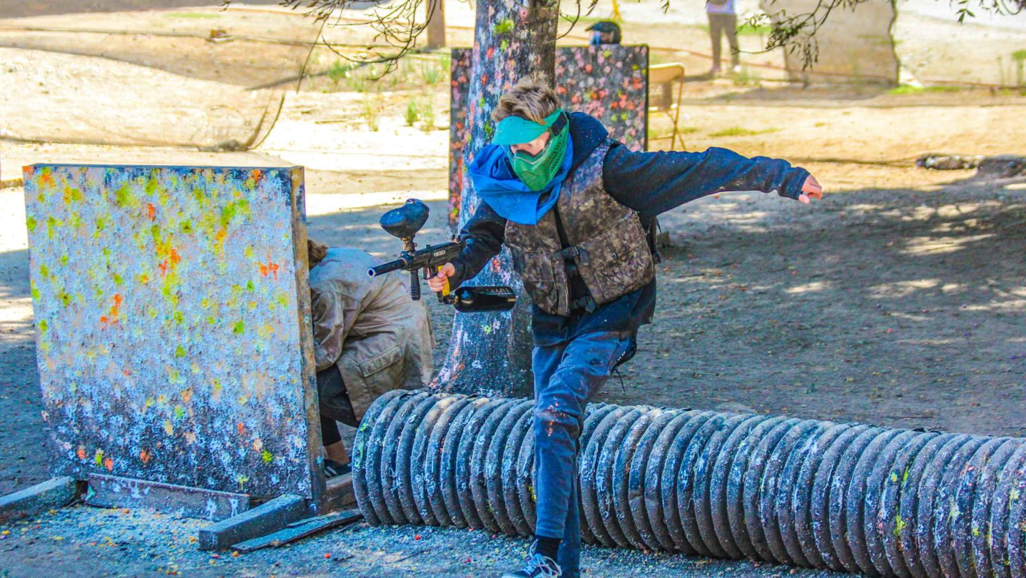 A camper running while playing paintball