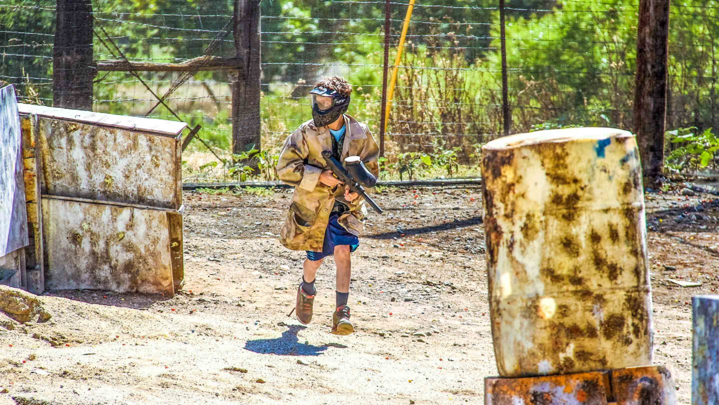 A camper running on the paintball course
