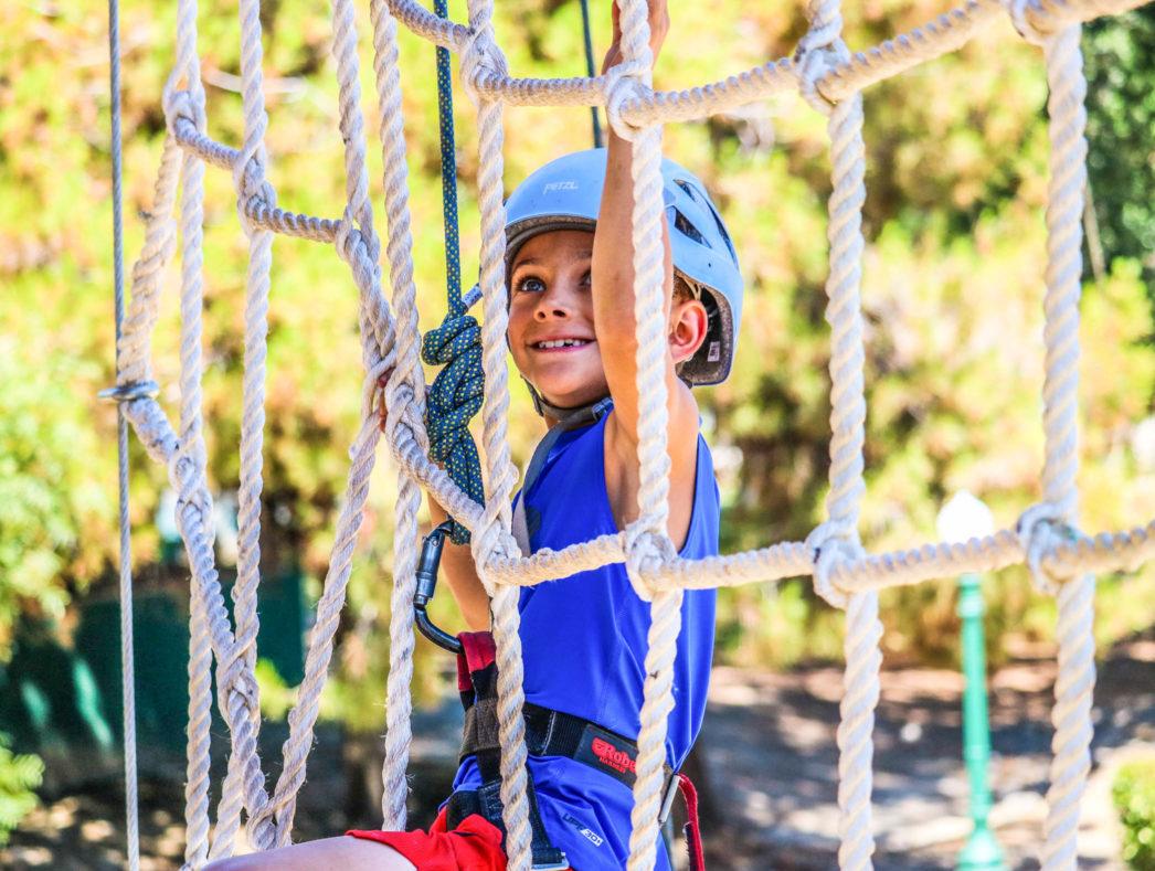 A camper climbing a rope net