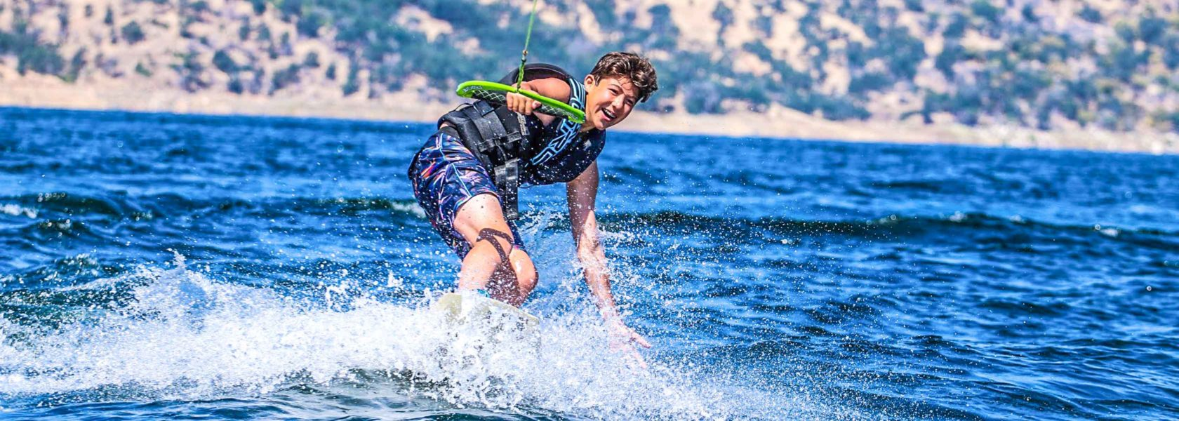 A camper having fun wakeboarding