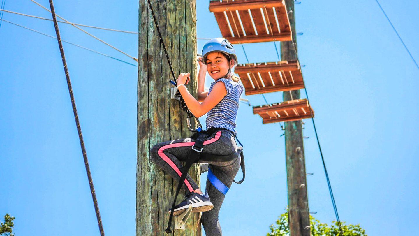 A camper climbing a ropes course