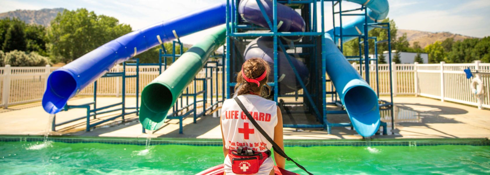 A lifeguard standing by the pool and water slide.